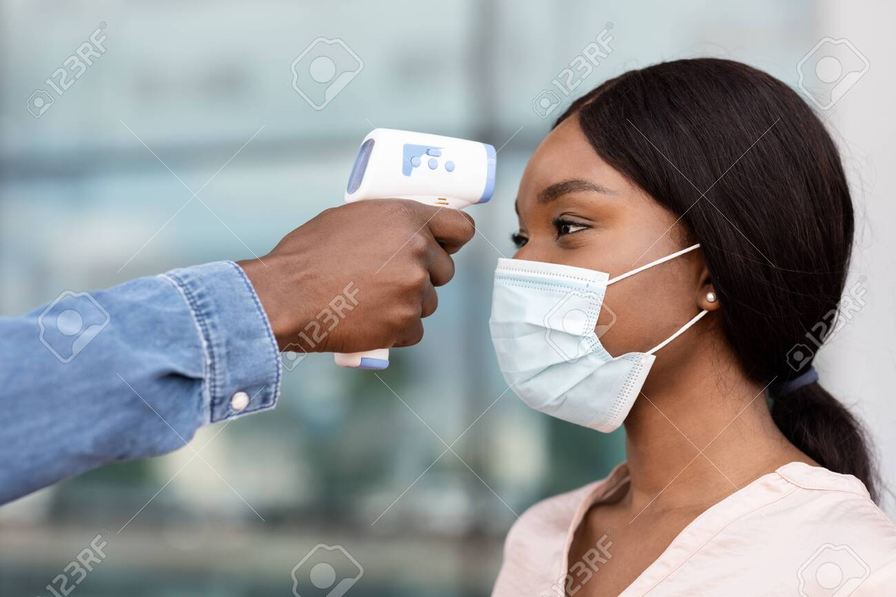 Security guard using digital medical electronic thermometer for black woman passenger in airport due to COVID-19, closeup - 154955129