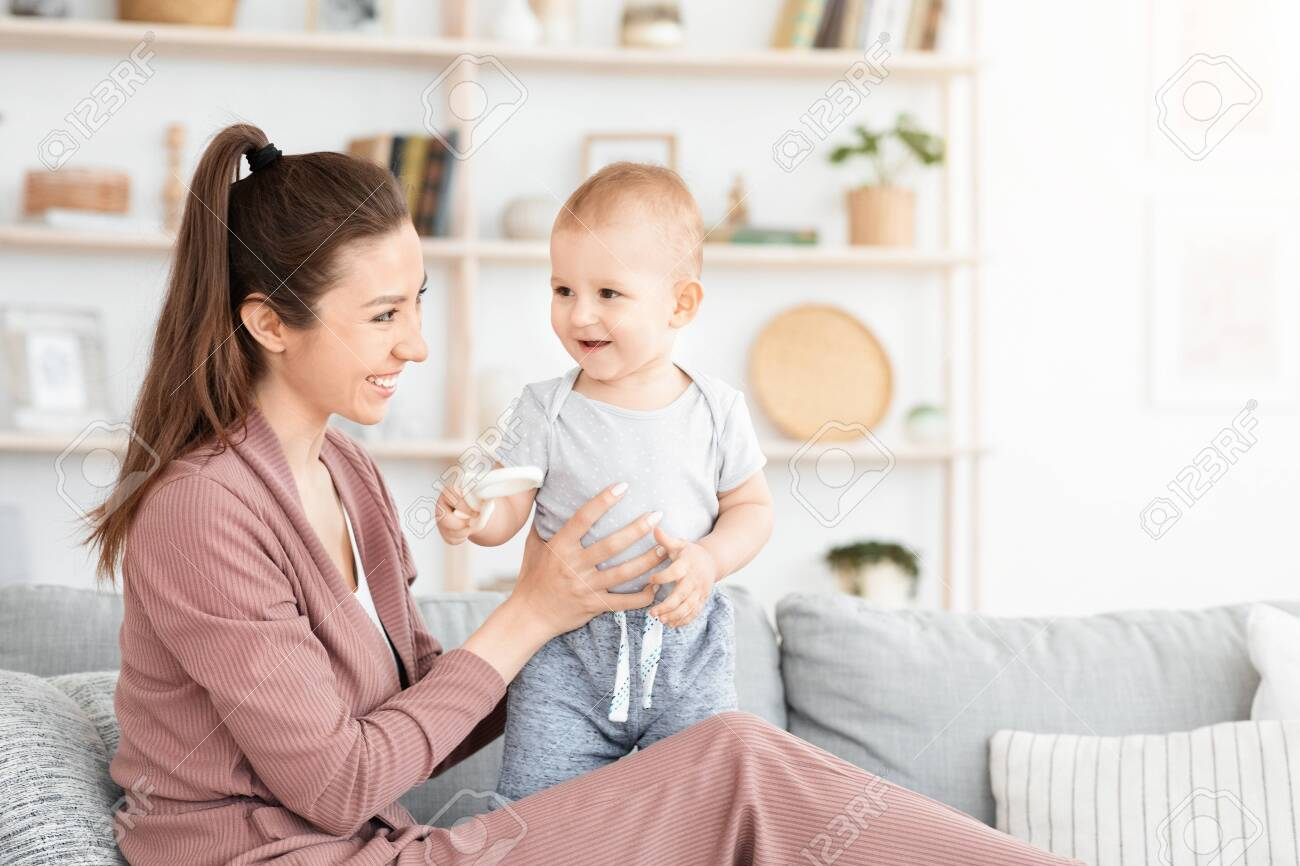 Portrait Of Mother And Toddler Baby Playing And Laughing Together At Home, Sitting On Couch In Living Room, Copy Space - 154956363
