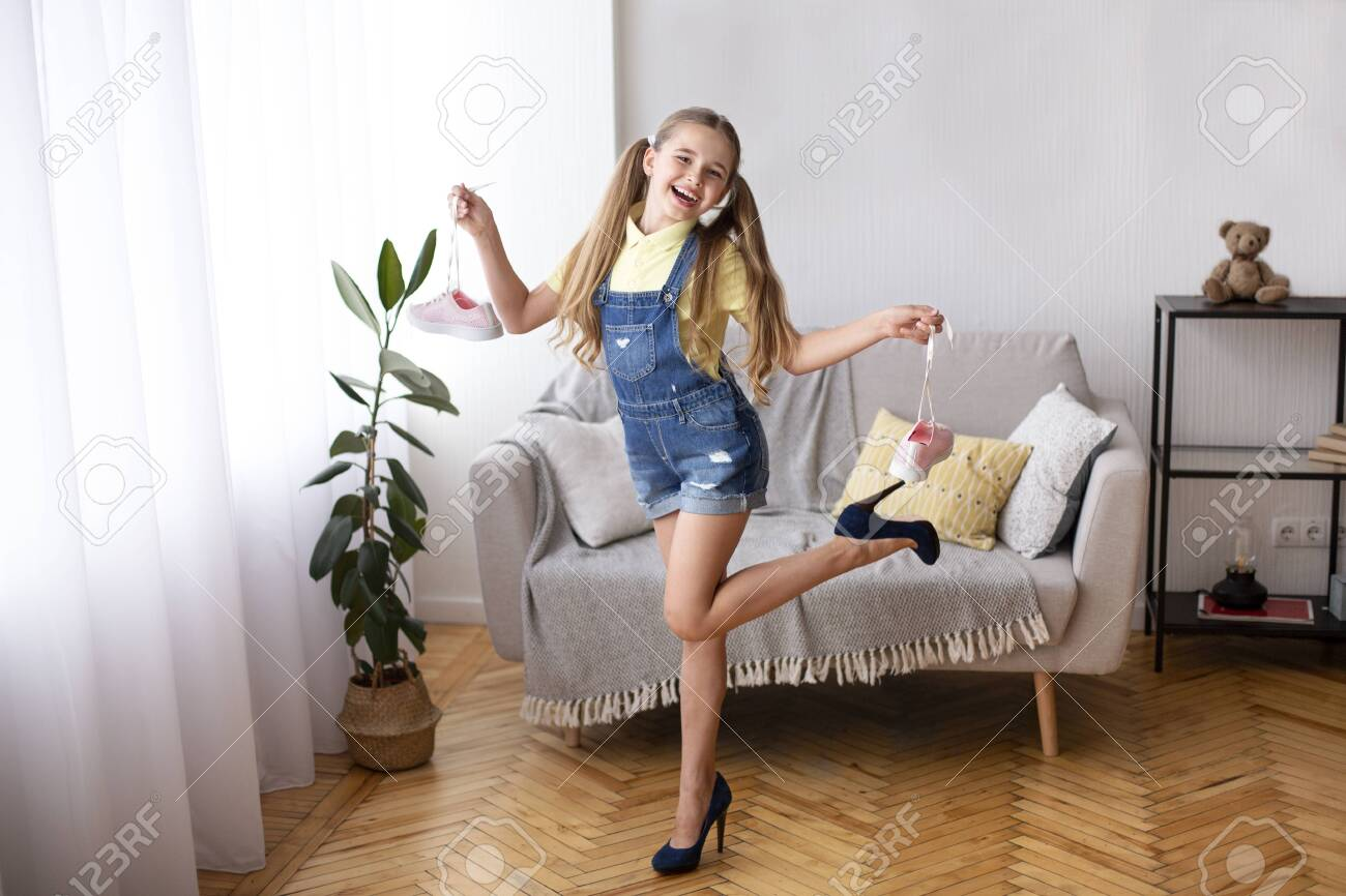 Full length portrait of excited teenager posing in blue high heels shoes, holding sneakers by laces - 154952264