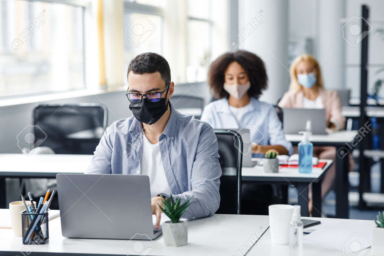 Teamwork in corporate company and returning to work after quarantine covid-19. Focused millennial man in glasses and protective mask works at laptop at workplace with antiseptic in office interior - 156529427