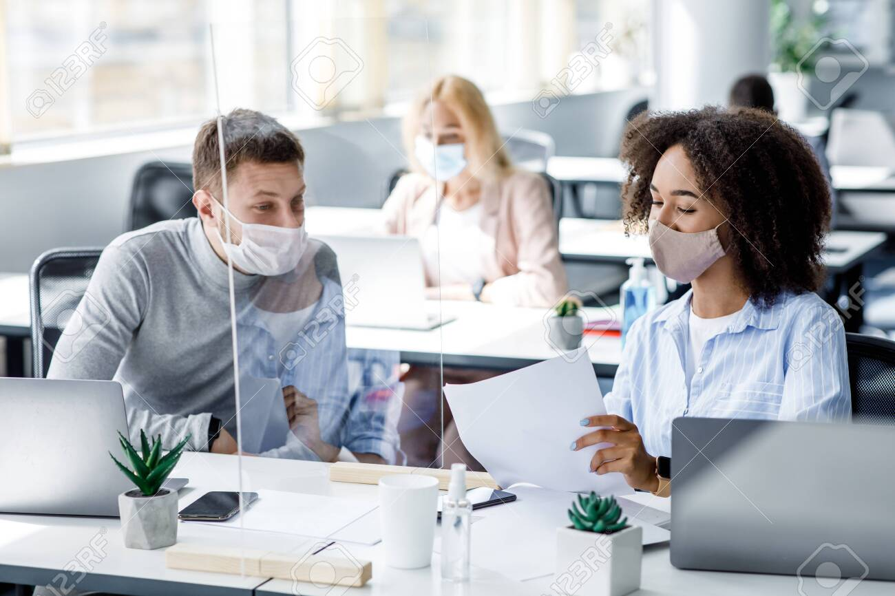 Protection employees on workplace. African american female in protective mask shows documents to guy at desk with laptops and antiseptics through protective glass in office interior during pandemic - 156561660