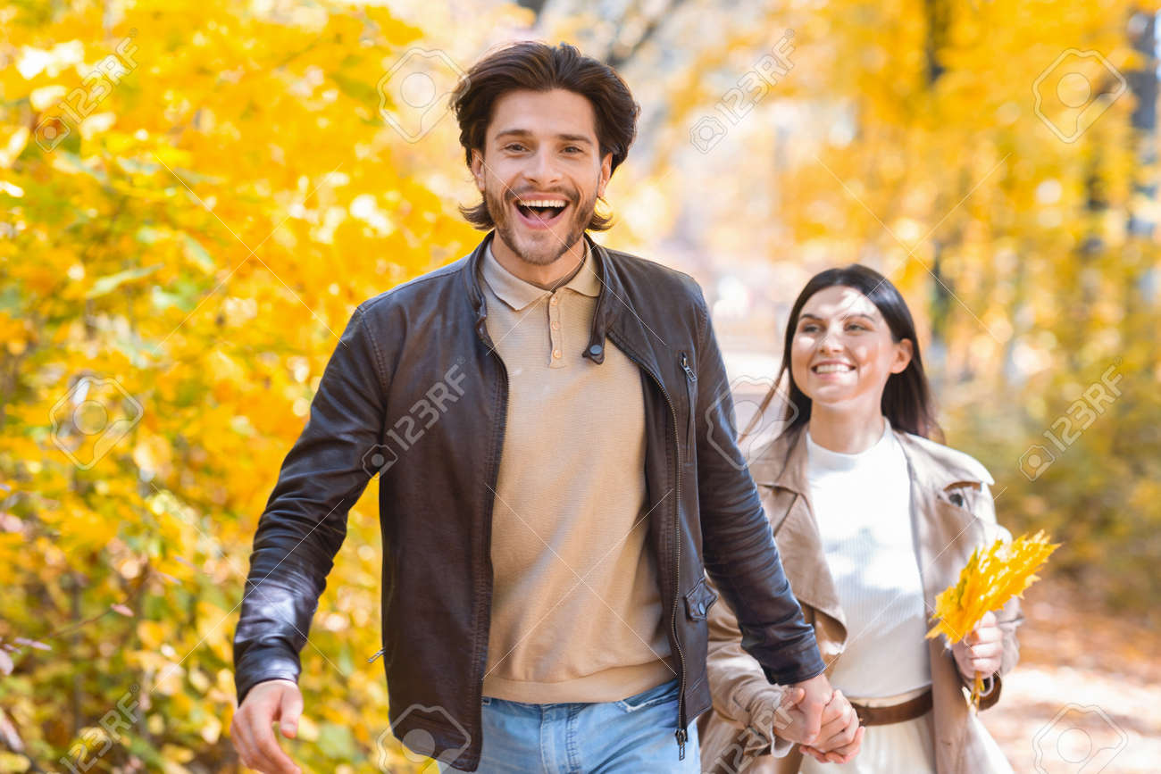 Emotional guy running buy golden autumn forest with his girlfriend, copy space - 156652508
