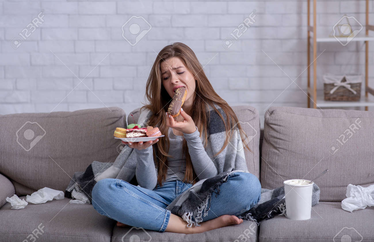 Comfort foods and stress eating concept. Frustrated young lady devouring pastry on sofa at home. Upset woman dealing with negative emotions, anxiety or problems through sweets - 157397990