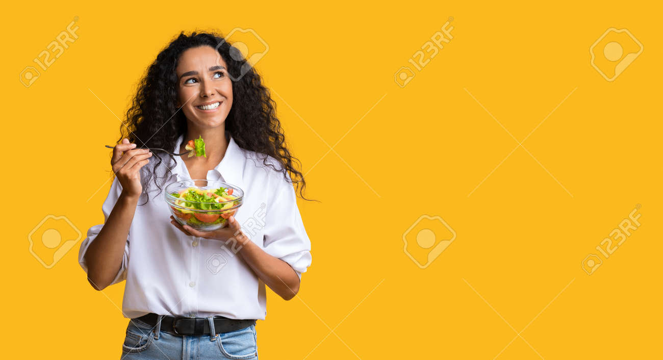 Cheerful Woman Eating Vegetable Salad From Bowl And Looking At Copy Space On Yellow Background, YoungLady Enjoying Heathy Nutrition And Organic Food, Having Vegetarian Meal For Lunch, Panorama - 157398045