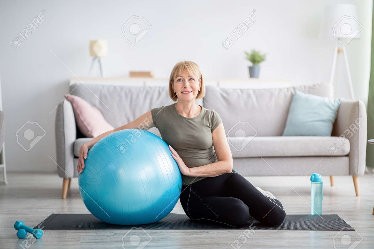 Full length portrait of happy mature woman resting on yoga mat with fitness ball, smiling at camera indoors, free space. Cheerful senior lady taking break from her domestic training - 166099572