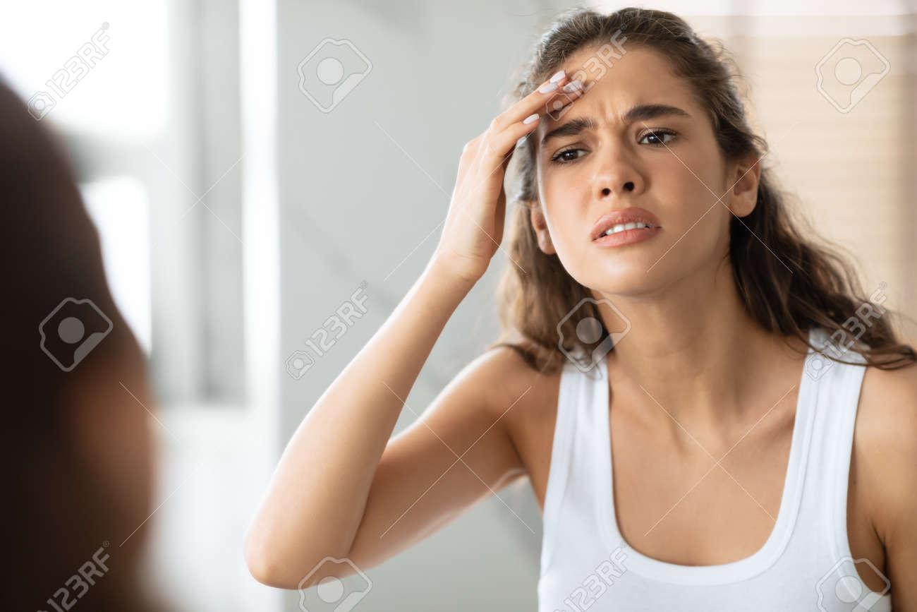 Concerned Woman Searching Wrinkles Looking At Forehead In Bathroom Indoor - 165680395