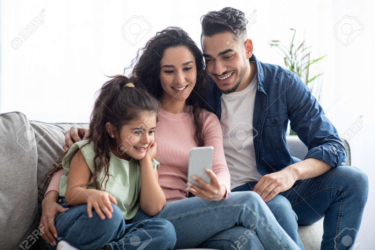 Happy arabic family of three using smartphone at home, relaxing on couch - 165745138