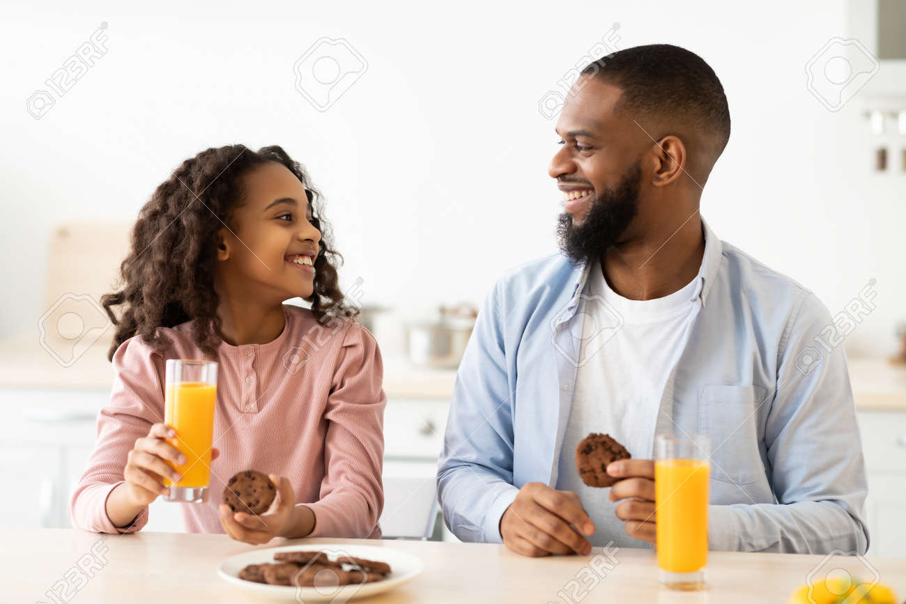 Cheerful african american daughter and dad having breakfast - 167855925