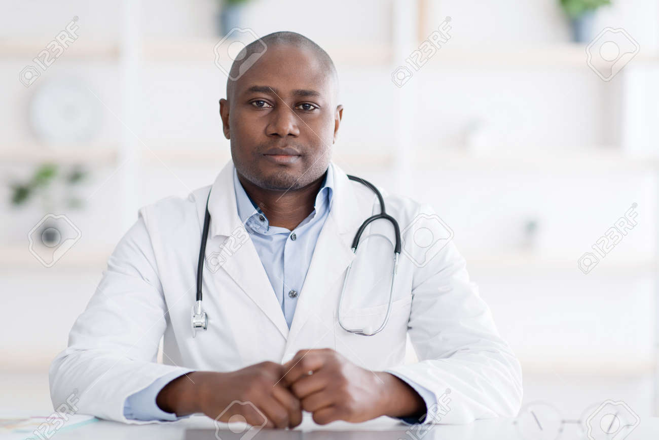 Portrait of confident african american doctor in white uniform looking seriously at camera, free space - 167836158