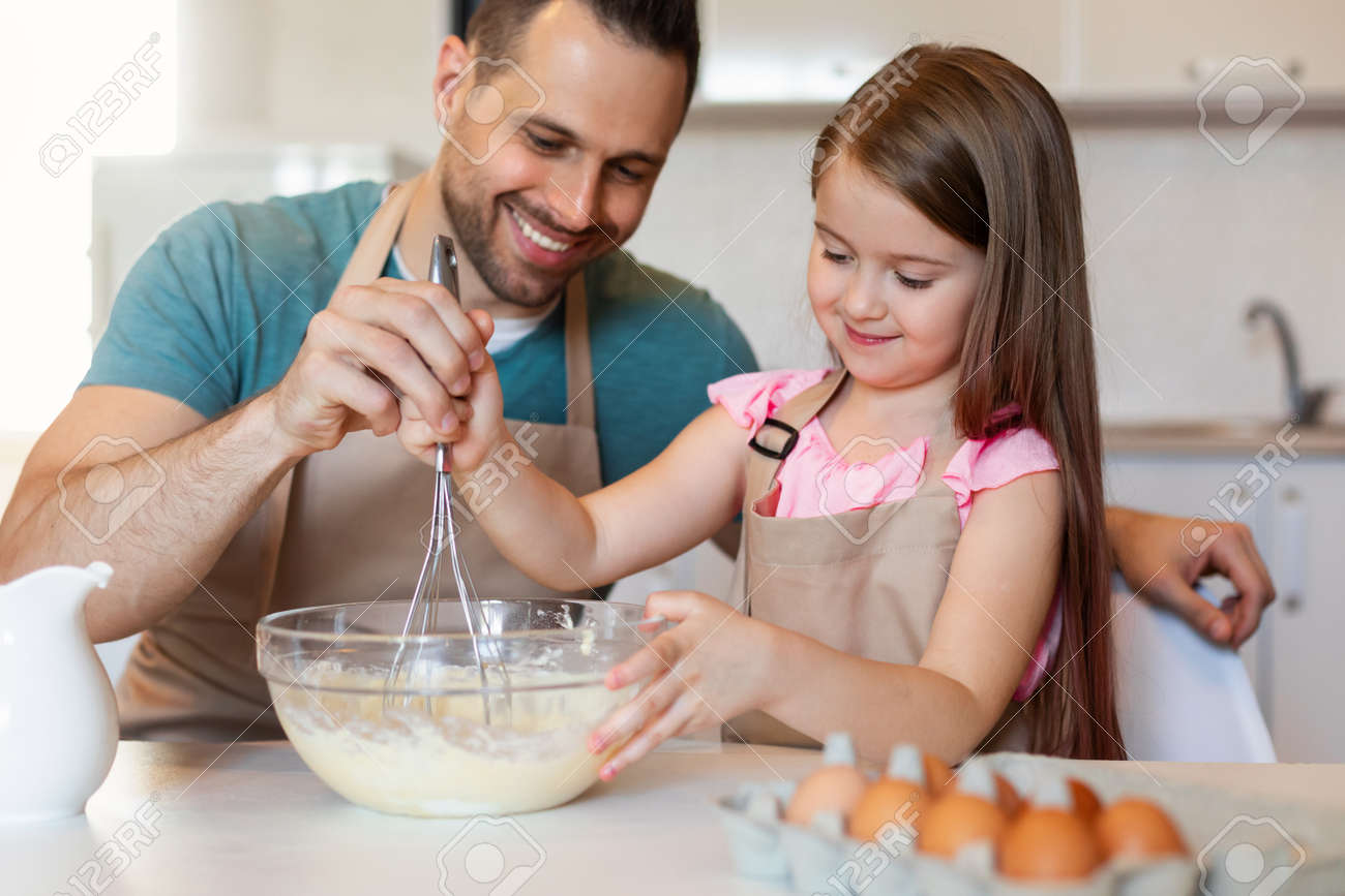 Cheerful Father And Daughter Cooking Pancakes Making Dough In Kitchen - 168062350