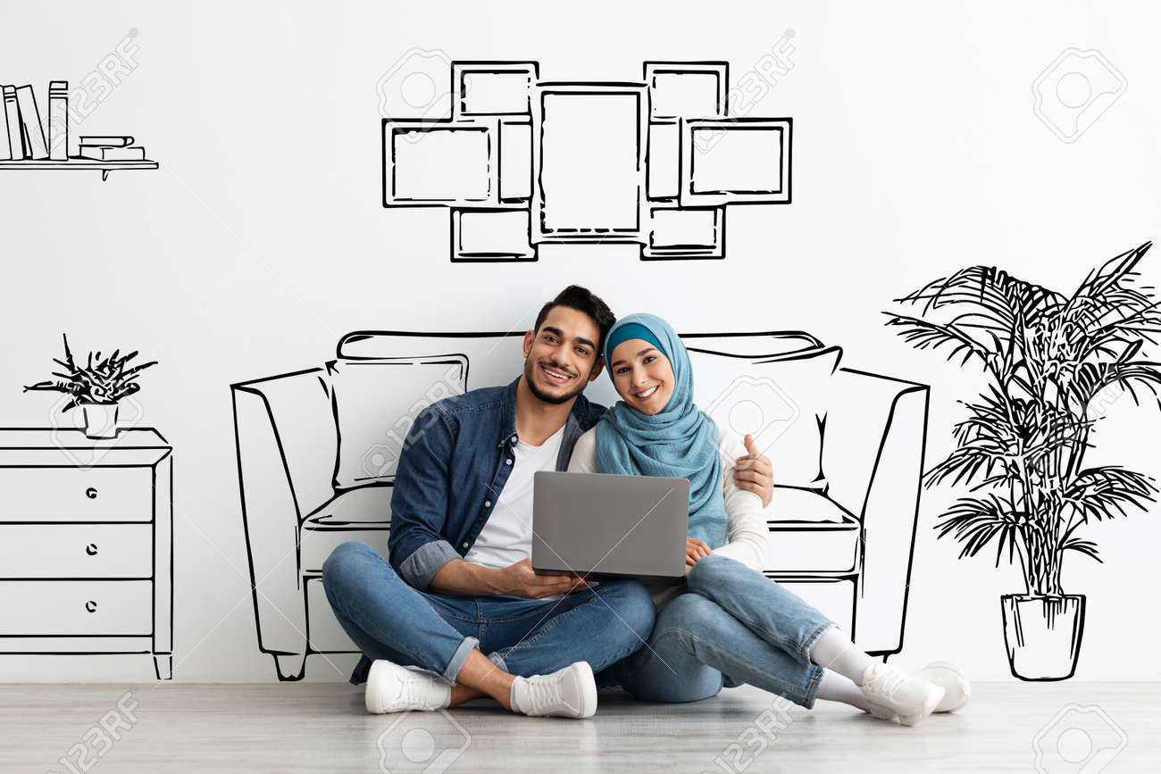 Happy muslim family sitting on floor with laptop - 168080374