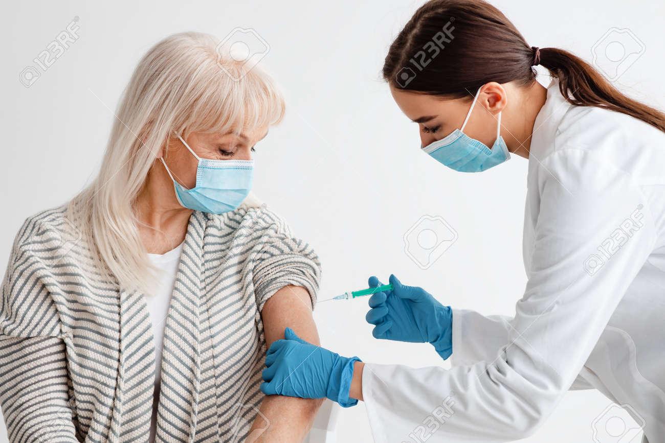 Senior Patient Receiving Vaccine Intramuscular Injection - 168076941