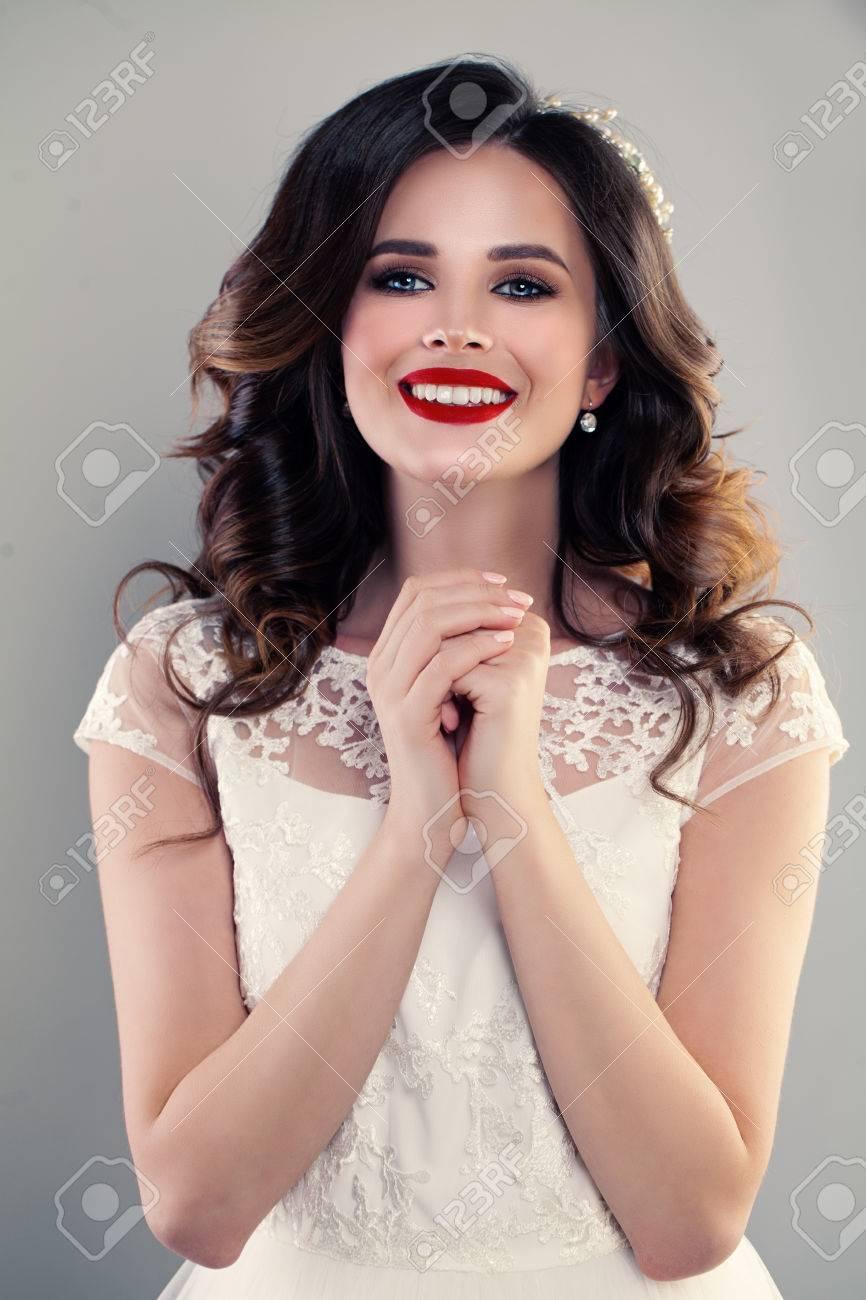 e1d18e42ffd Banque d images - Magnifique modèle de mode femme portant une robe blanche.  Happy Girl avec cheveux bouclés et maquillage