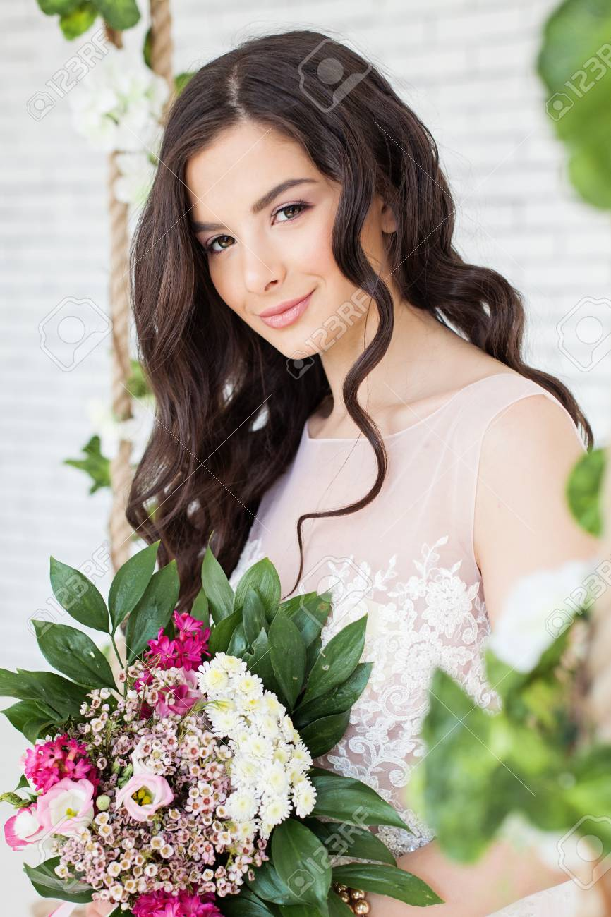 Beautiful woman with flowers curly hairstyle and makeup brunette beautiful woman with flowers curly hairstyle and makeup brunette model girl stock photo izmirmasajfo Image collections