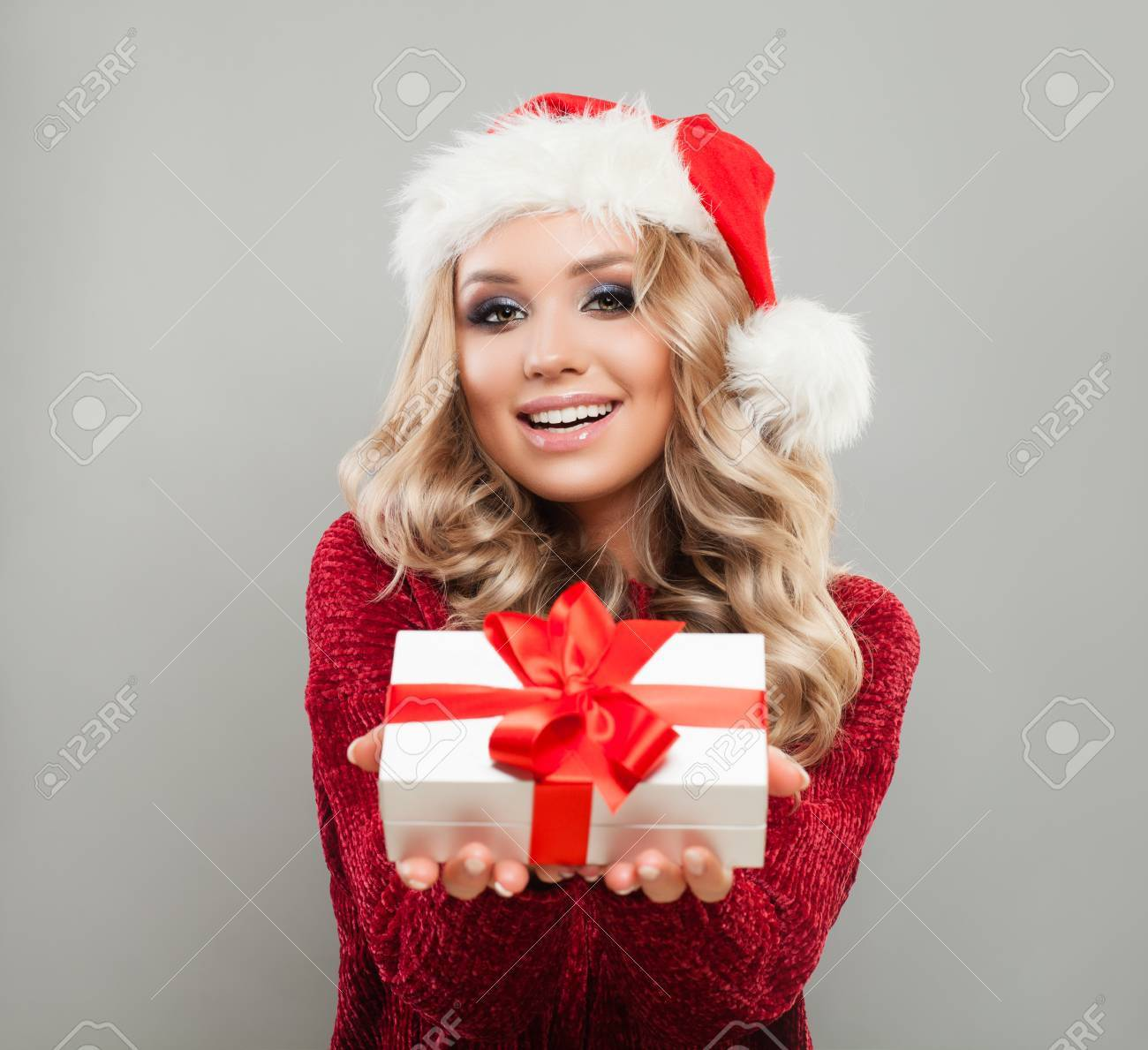 8274948f66a2f Christmas Woman in Santa Hat Holding White Xmas Gift Box with Red Ribbon. Happy  Model