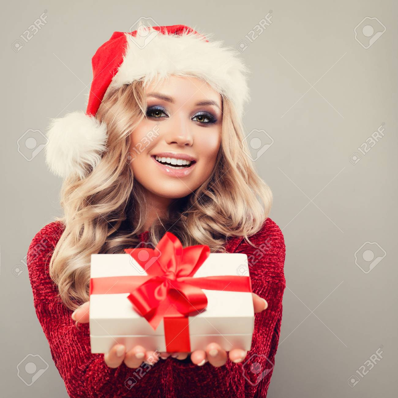 e6f1ae30472bd Smiling Model Woman wearing Santa Hat and Holding Christmas Gift on  Background with Copy space.
