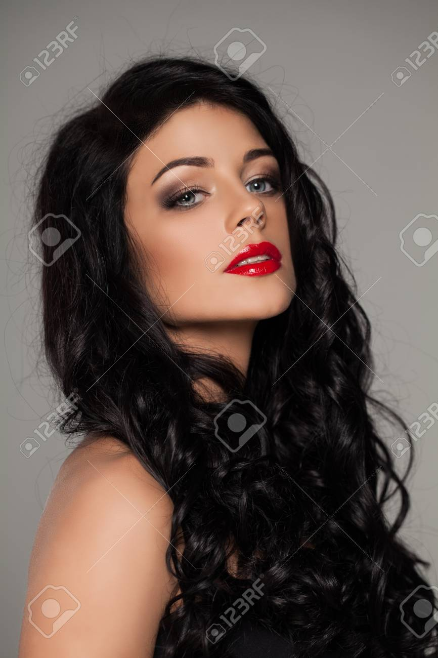 Gorgeous Woman With Dark Curly Hair And Red Lips Makeup