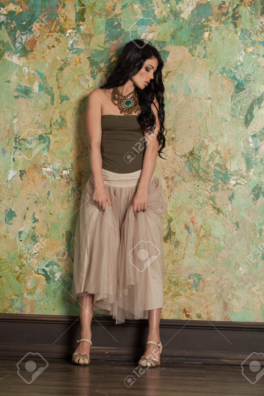 b6bf95d09aa Stock Photo - Young Perfect Brunette Woman wearing Trendy Clothes and High Heels  Sandals on Green Wall Background. Fashion Photo