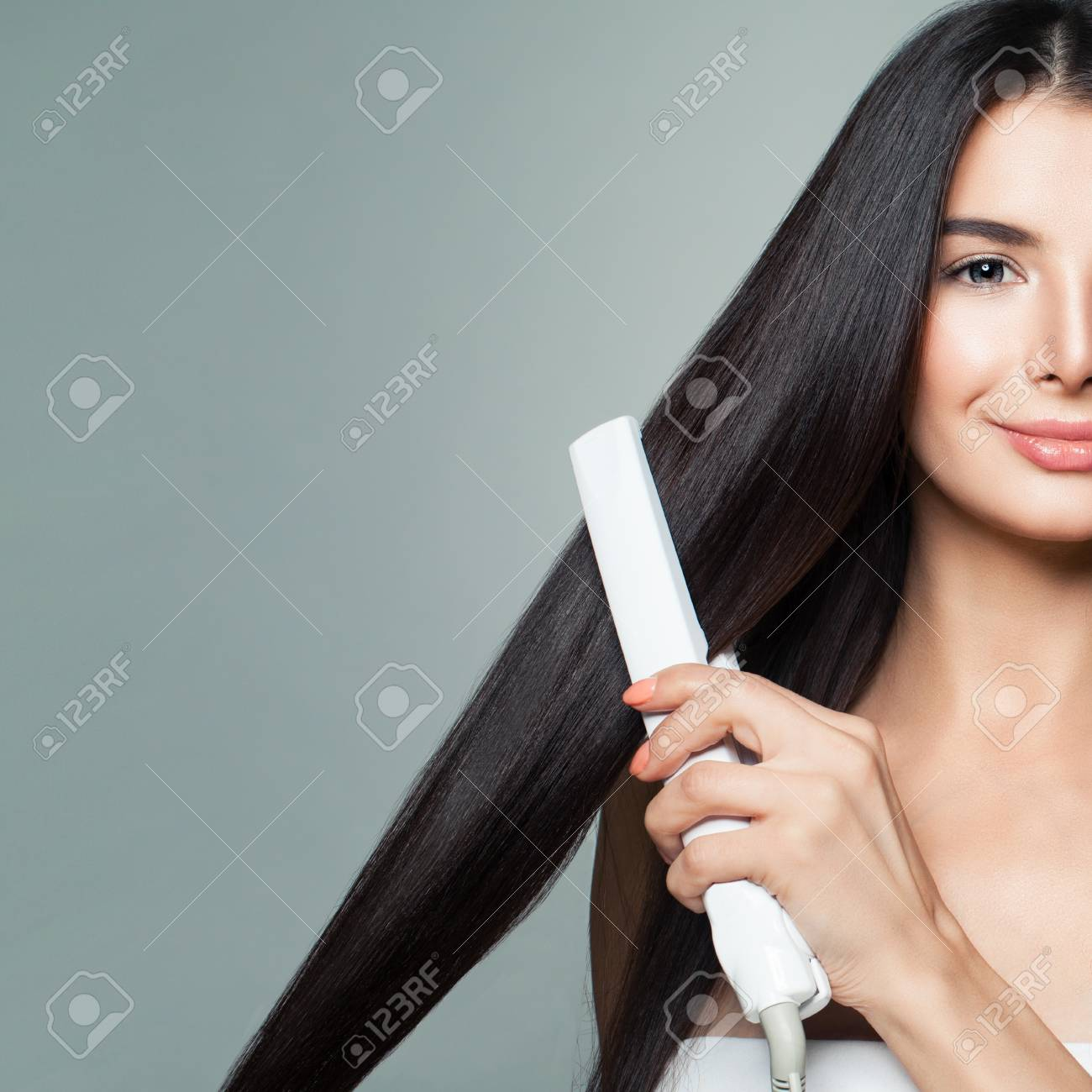 Beautiful Woman with Long Straight Hair Using Hair Straightener. Cute Smiling Girl Straightening Healthy Brown Hair with Flat Iron on Gray Background. Closeup Portrait - 97517182
