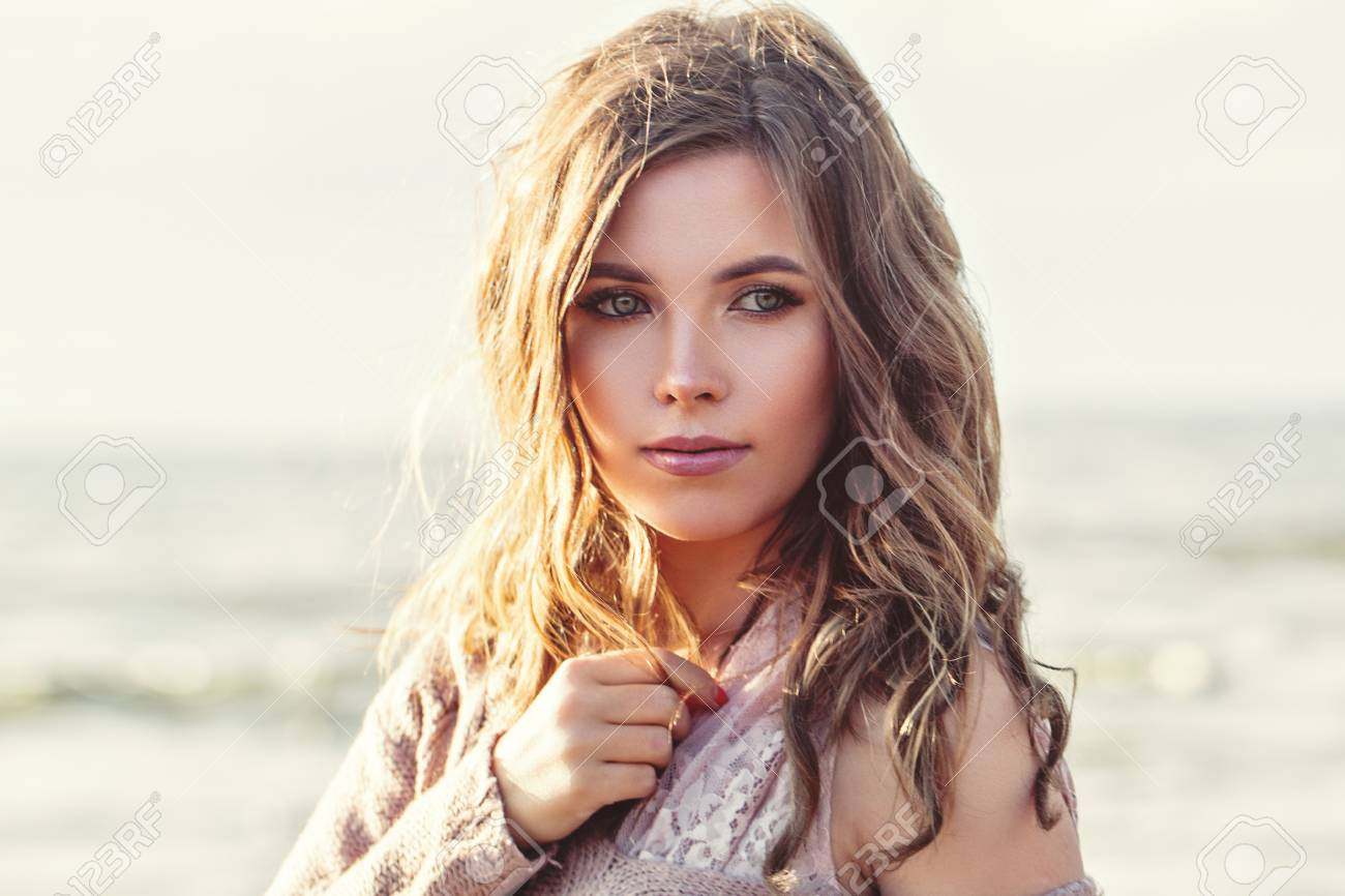 Beautiful woman face closeup portrait. Pretty girl with long curly brown hair on ocean background. Perfect natural beauty - 122127277