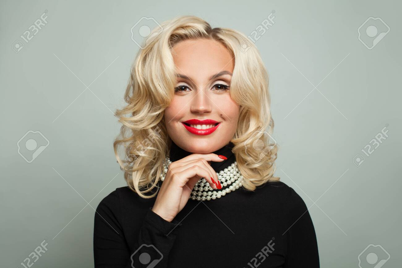 Perfect woman in pearls necklace holding her hand with manicured nails near face - 152779828