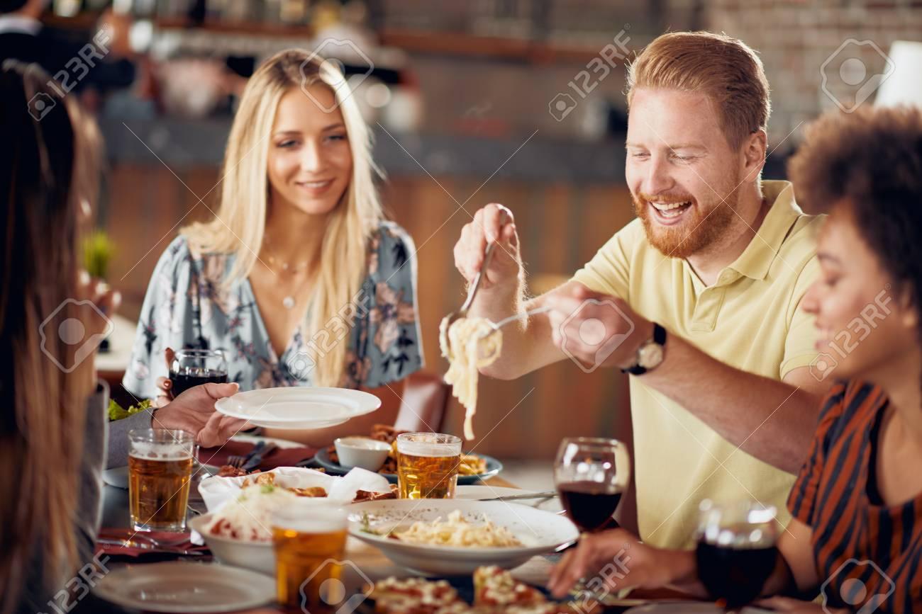 Friends having dinner at restaurant. Multi ethnic group. - 125829524