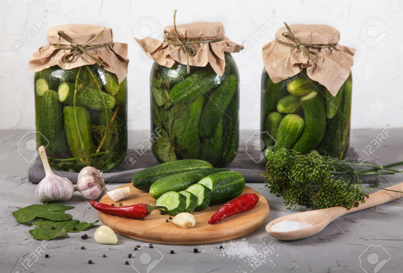 Three large glass jars with fermented cucumbers, cut cucumbers on a wooden board stand on a concrete gray background. horizontally - 151973583