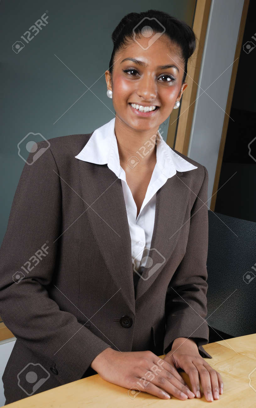 This is an image of a business woman smiling confidently at a reception desk. Stock Photo - 9436713