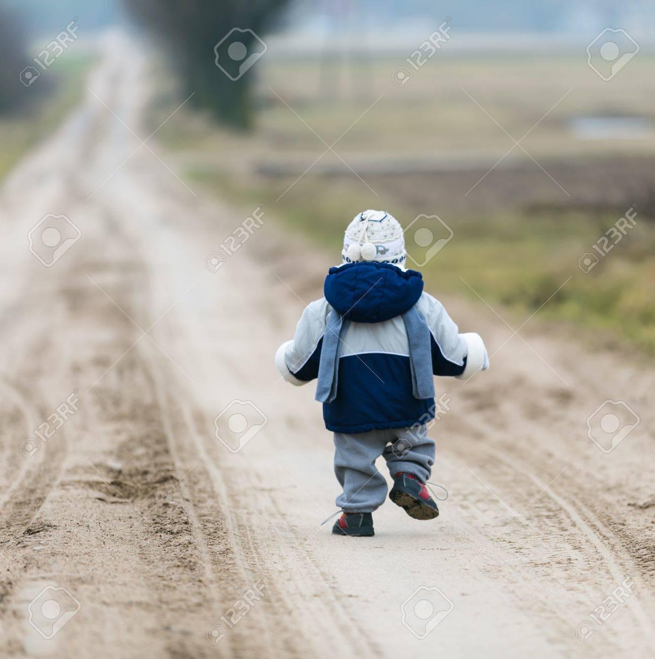 Little child walking self by rural sandy road - 37471783