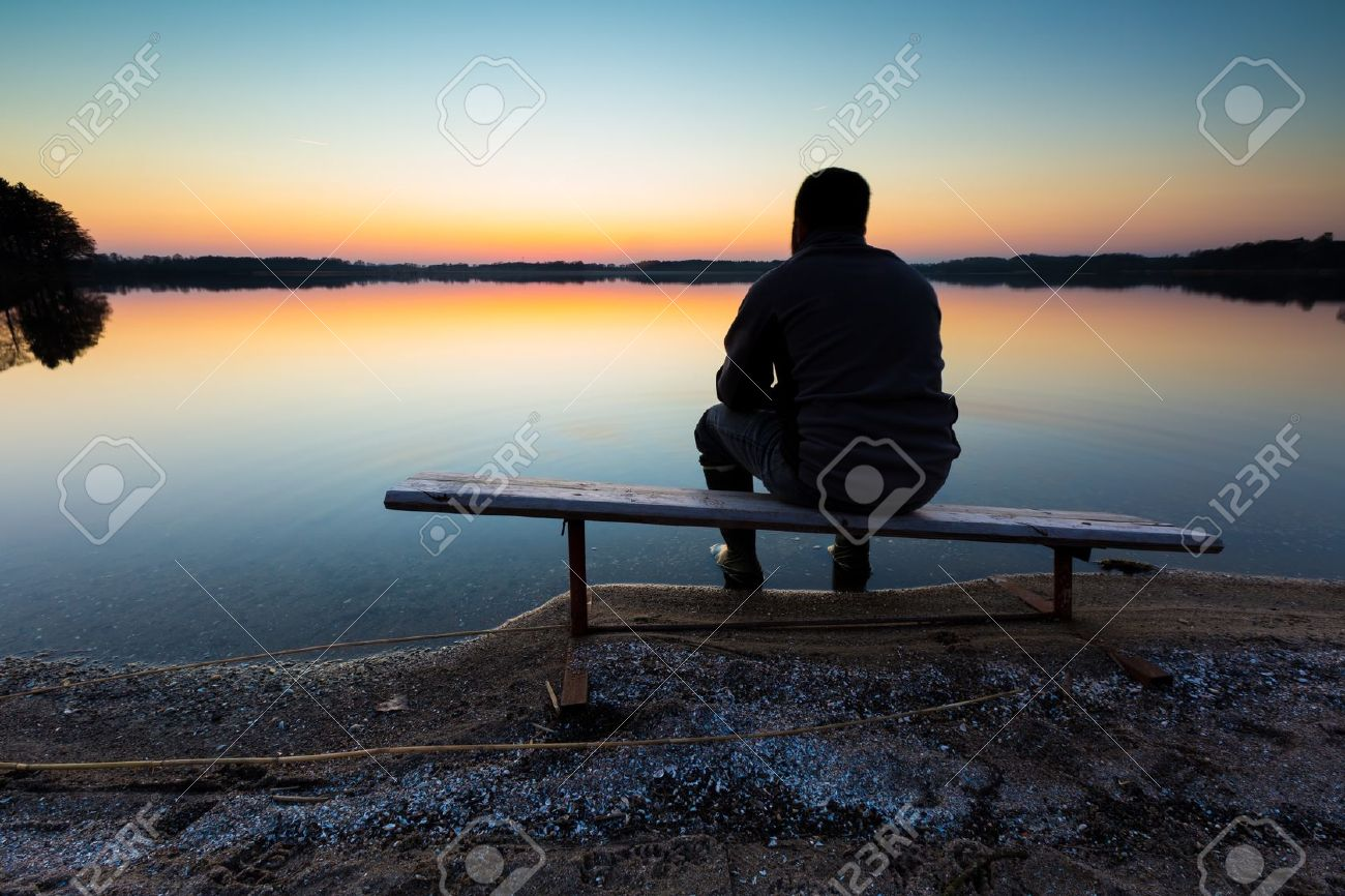 Bench on lake shore at sunset. Beautiful landscape with one man sitting and looking on sunset. Photographed in Poland. - 37944746