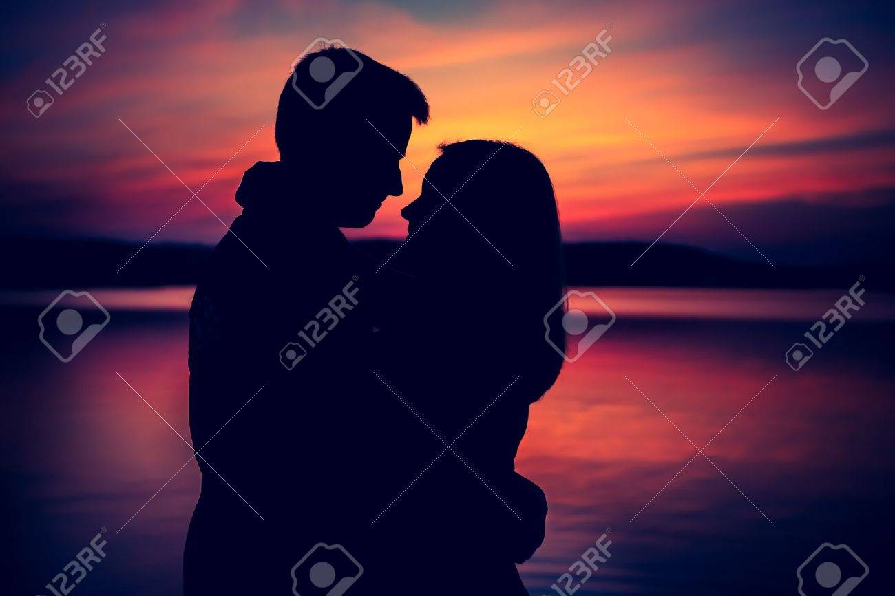 Silhouettes of hugging couple against the sunset sky. Photo with vintage mood. - 38511789