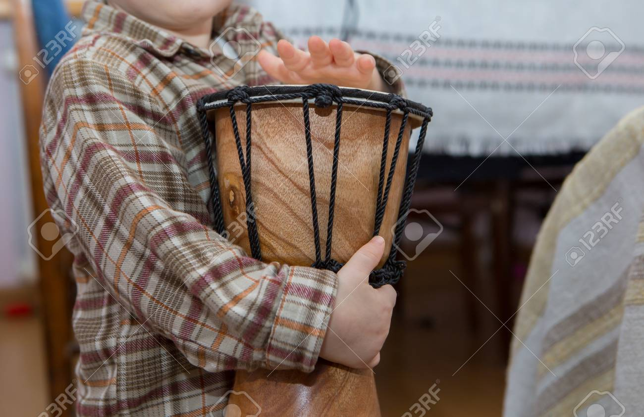Small child playing on drum. Little caucasian boy and drum. Hands close up - 49470336