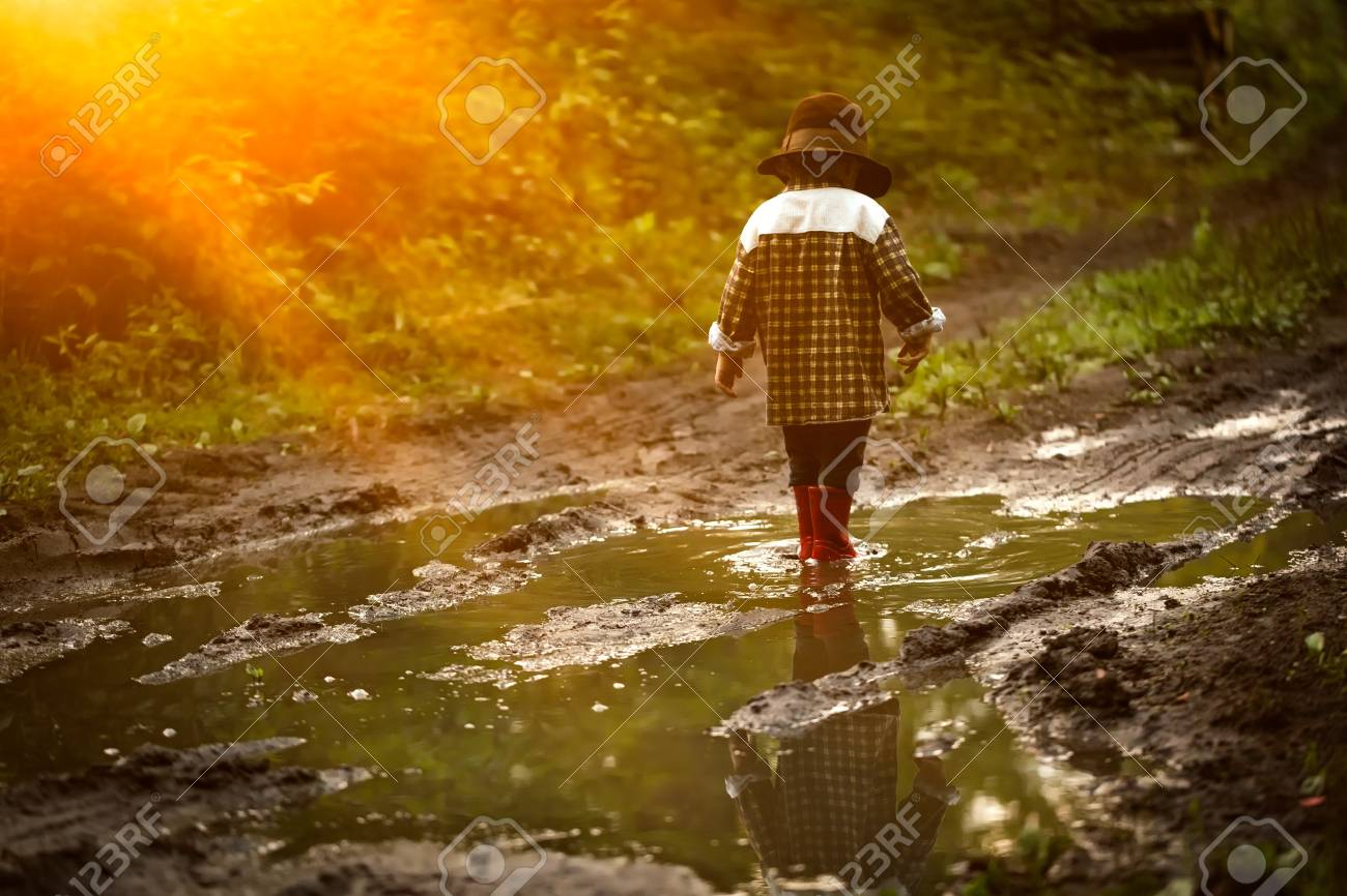 Little boy in hat and rubber shoes playing in puddle in summer forest. - 61267008