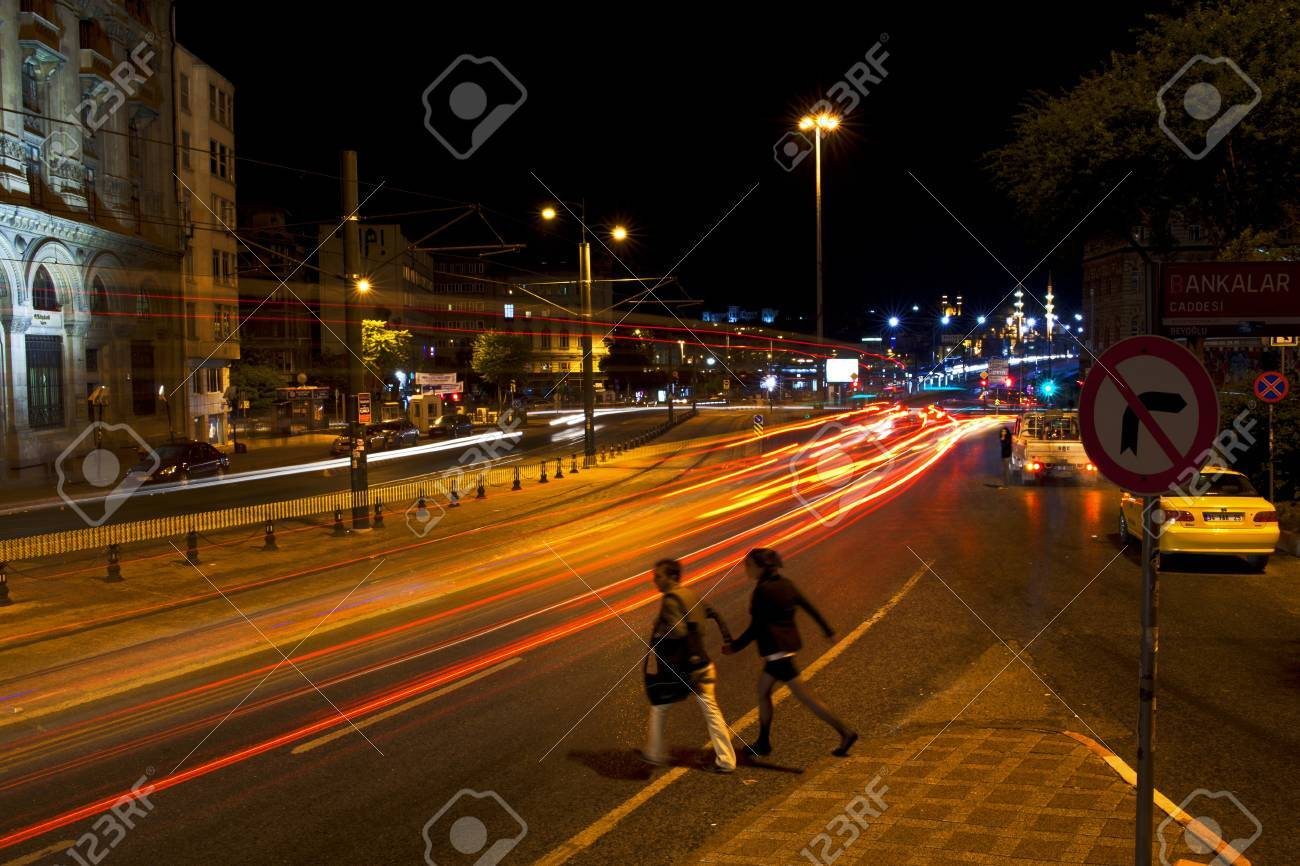 Istanbul, Karakoy, Turkey - May 29, 2012  A couple passing by the street  Cars lights are visible at the long exposure image and some historical buildings at Istanbul,Karak�y District,Turkey  Also two cars some of theme is a taxi waiting right side of the Stock Photo - 21294221