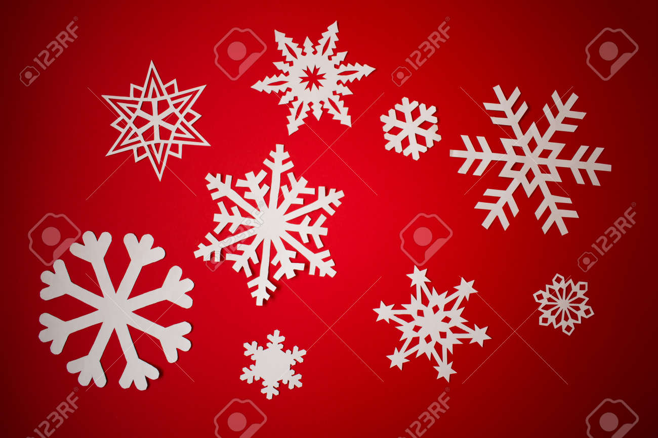 Various paper cut out snowflakes on red background - 159716097
