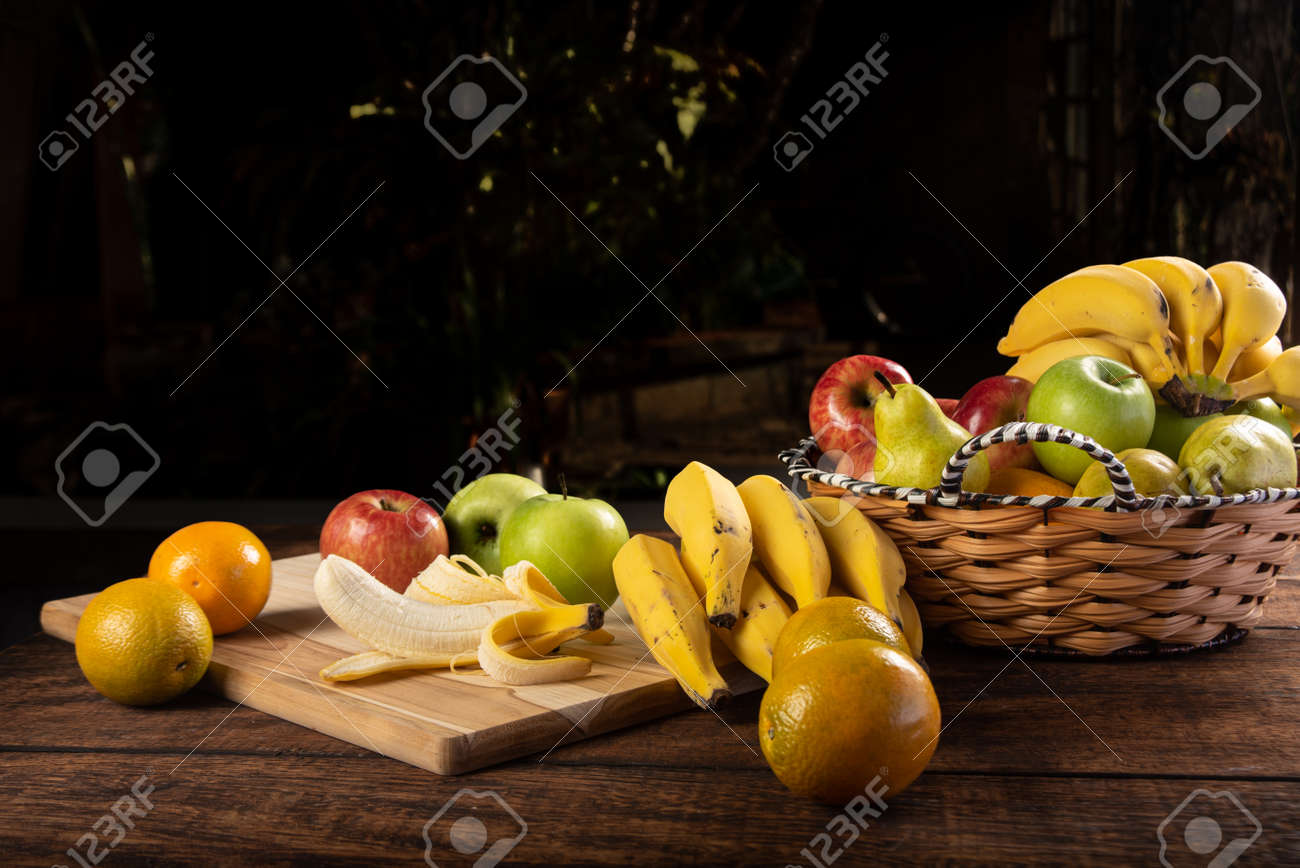 Peeled banana and apples on polished wood, placed on rustic wood with selective focus. - 153503291