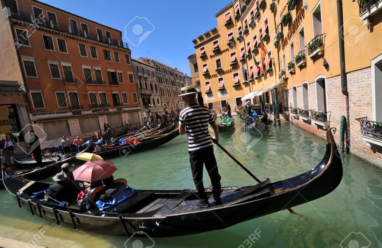 Venice, Italy - 7 May, 2012: Tourists sightseeing in gondola across Venetian canal Stock Photo - 14145131