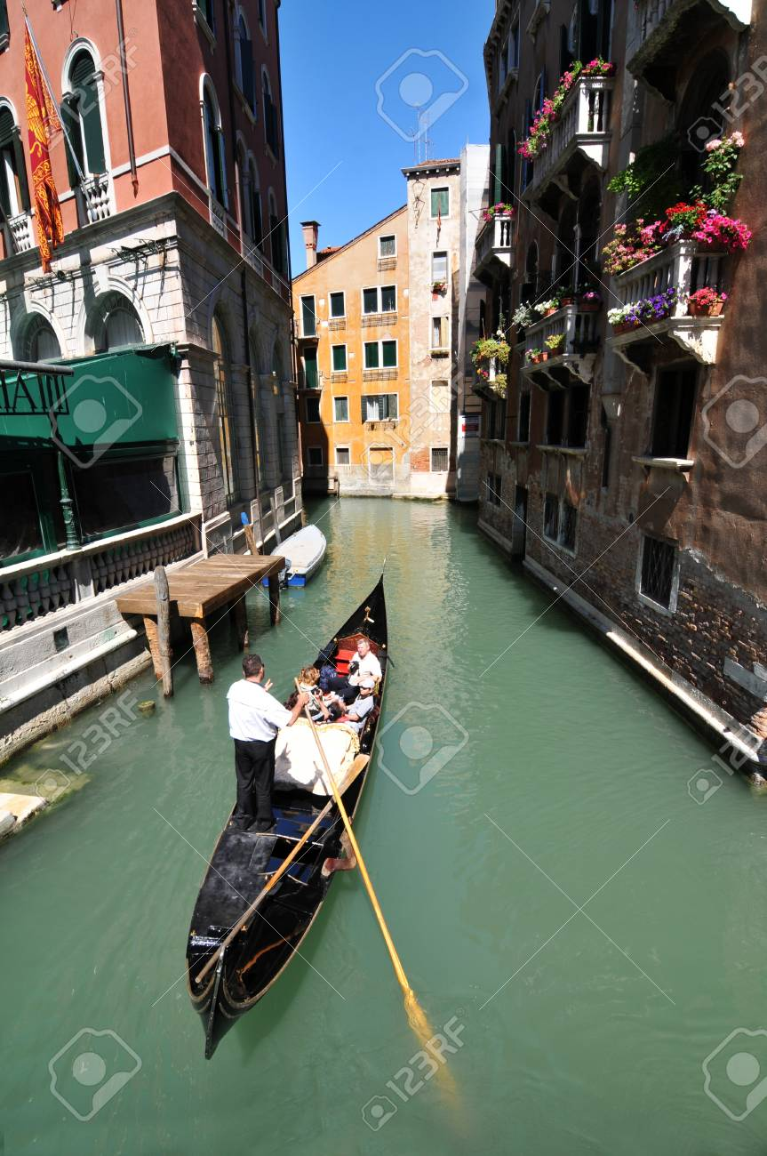 Venice, Italy - 7 May, 2012: Tourists sightseeing in gondola across Venetian canal Stock Photo - 14145125