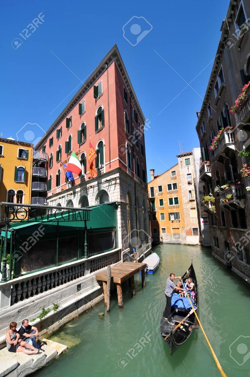 Venice, Italy - 7 May, 2012: Tourists sightseeing in gondola across Venetian canal Stock Photo - 14145124
