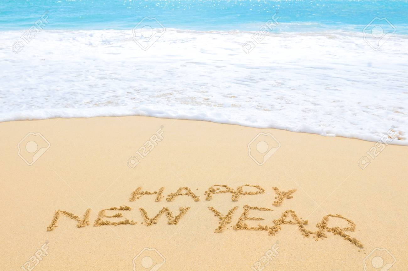 Happy New Year written on sand of an exotic beach - 96390335