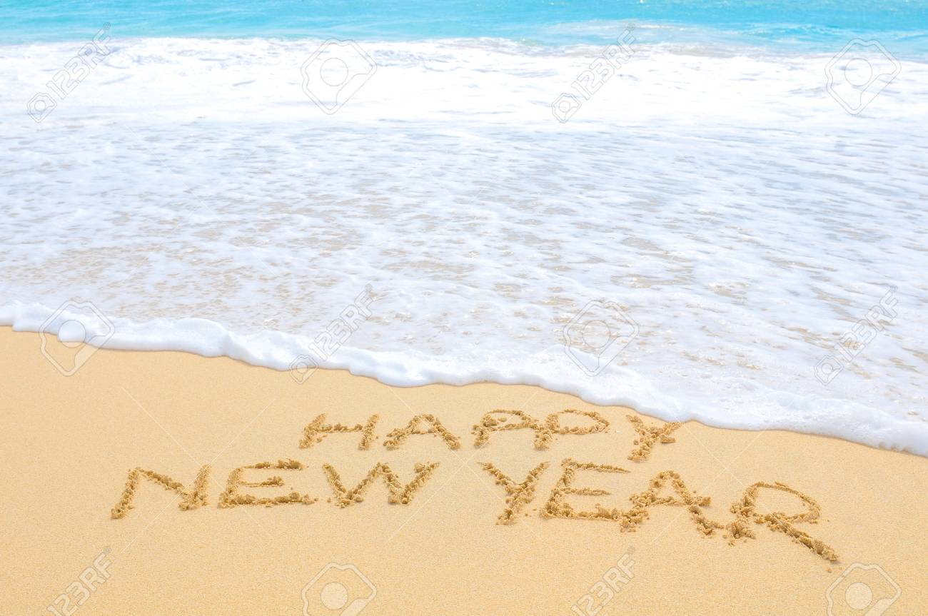 Happy New Year written on sand of an exotic beach - 96362063