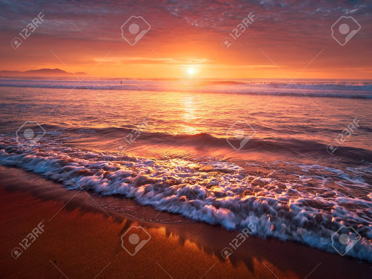 beautiful red sunset on beach with a wave on the shore - 131949471