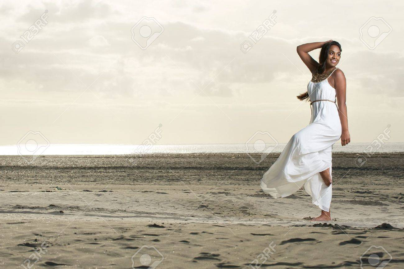An african girl doing a dance pose with a smile at the beach Stock Photo - 15921230