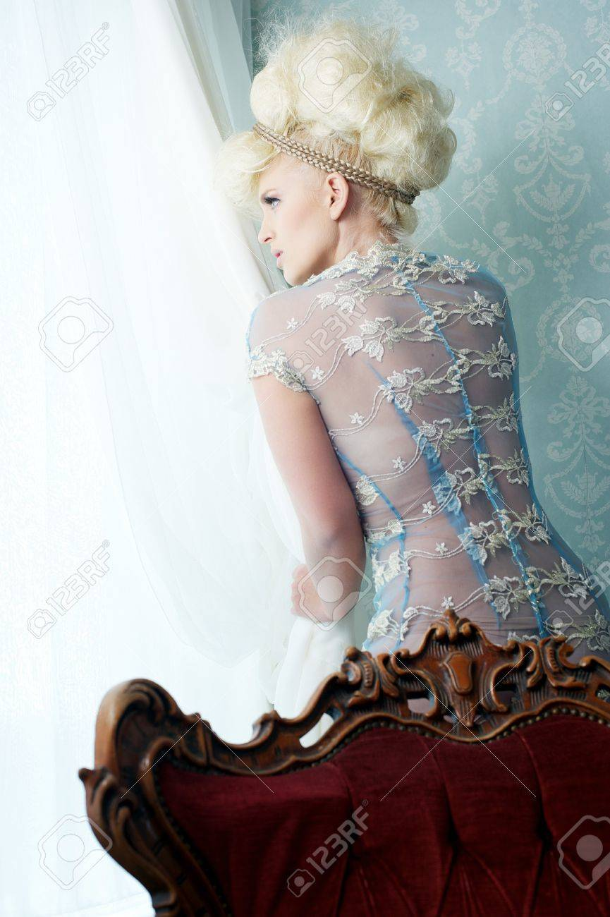 Beautiful european blond woman in sexy dress is looking outside Stock Photo - 15938420