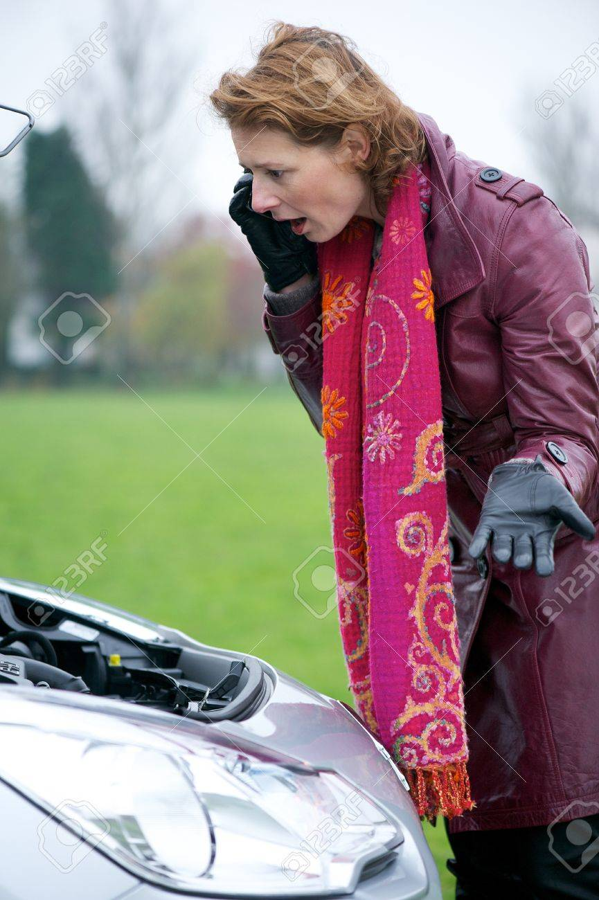 Worried Caucasian woman on mobile phone. She is looking under the hood of her broken down car with engine failure Stock Photo - 16639902