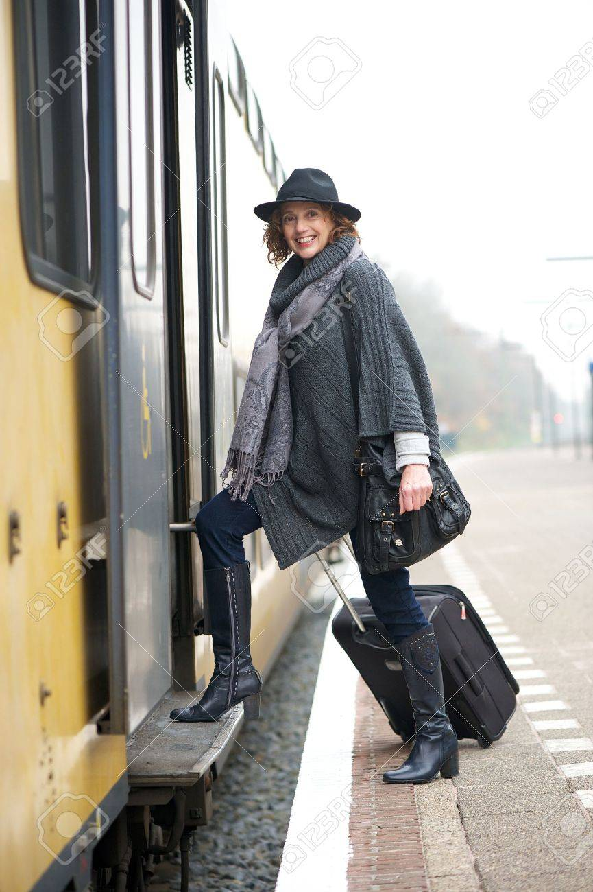 Traveling woman with suitcase luggage is boarding the train from the platform and smiling at the camera Stock Photo - 16639939