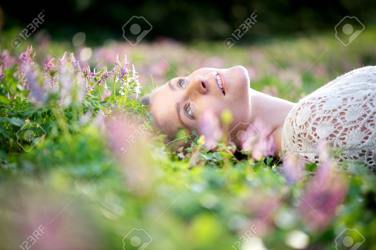 Portrait Of A Beautiful Young Woman Lying In Meadow Of Flowers Stock