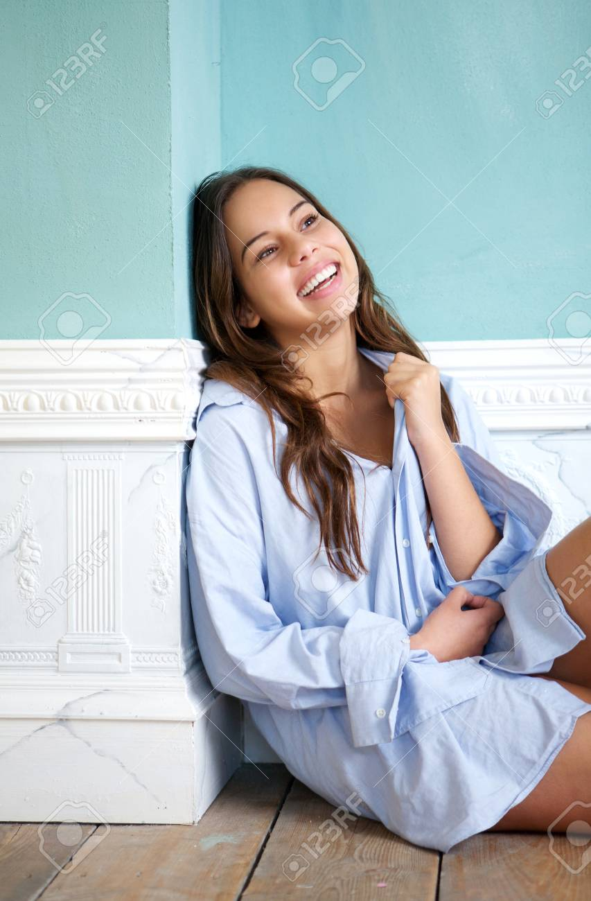 Close up portrait of a happy woman sitting on wooden floor and laughing at home Stock Photo - 23954483