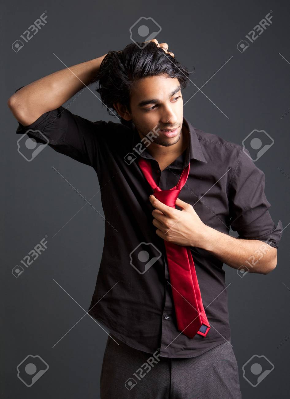 56cc3a0a6458 Portrait of a young man with black shirt and red tie posing with hand in  hair