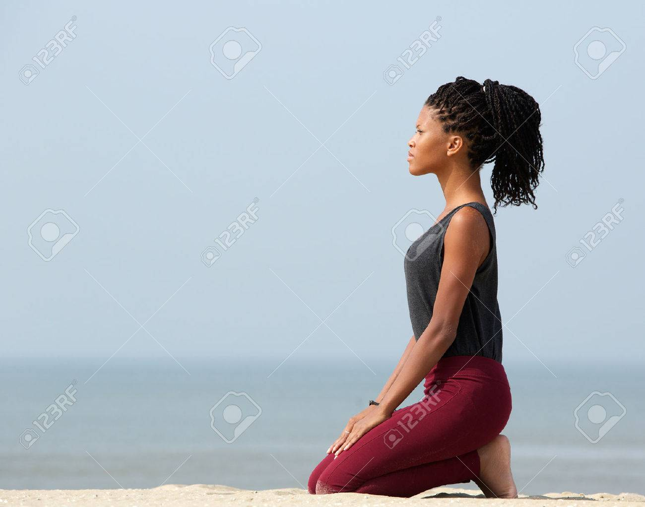 side view portrait of a young woman meditating at the seaside stock